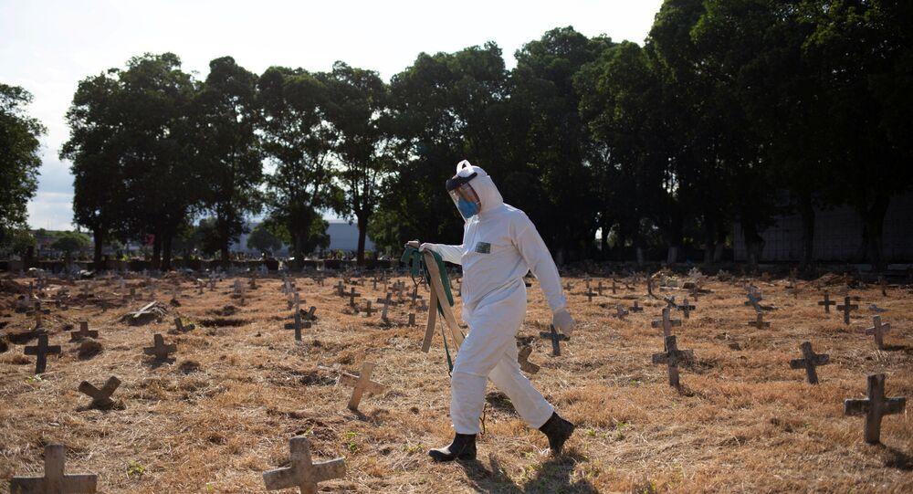 Coveiro com roupa de proteção enterra mortos de causa desconhecida em meio à pandemia de coronavírus em cemitério no Rio de Janeiro