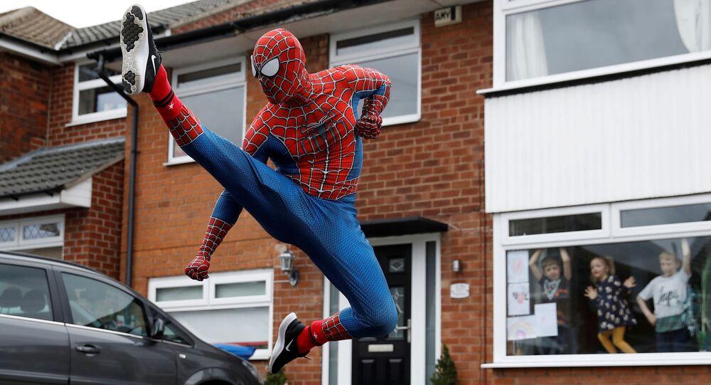 Homem fantasiado de homem-aranha tenta distrair crianças em quarentena, no Reino Unido, 1º de abril de 2020