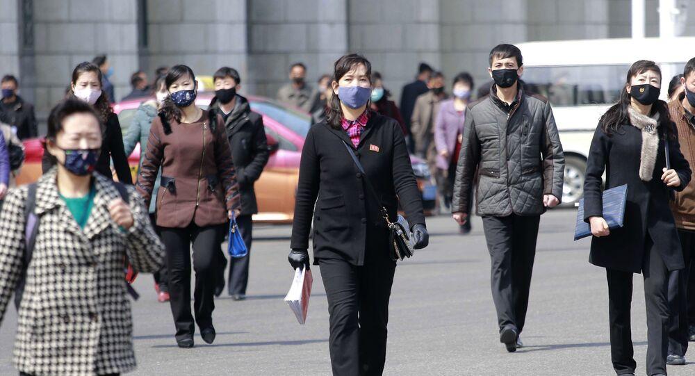 Pedestres caminham de máscaras protetoras na capital da Coreia do Norte, Pyongyang, 1º de abril de 2020