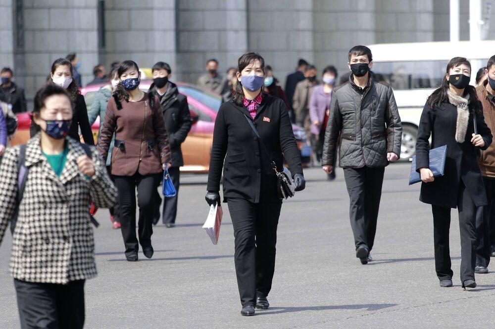 Pedestres com máscaras protetoras em uma rua da capital norte-coreana, Pyongyang