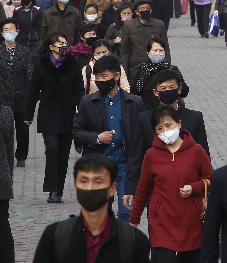 Pessoas caminham com máscaras para se proteger do coronavírus em rua do centro da capital da Coreia do Norte, Pyongyang