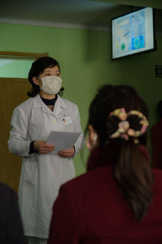 Médica explica medidas de prevenção do coronavírus em sala de espera de hospital na Coreia do Norte