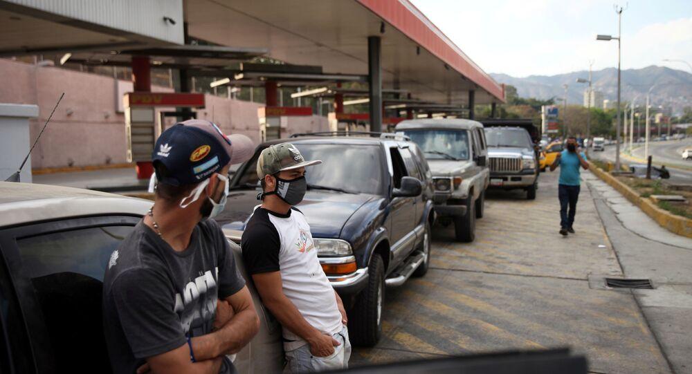 Pessoas usando máscaras se encostam em um carro estacionado em um posto de gasolina, durante a quarentena nacional contra propagação da COVID-19, em Caracas, Venezuela, 30 de março de 2020