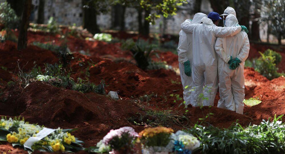 Coveiros com trajes de protecção reúnem-se no cemitério de Vila Formosa, o maior cemitério do Brasil, durante o surto de doença do coronavírus em São Paulo, Brasil, 2 de abril de 2020