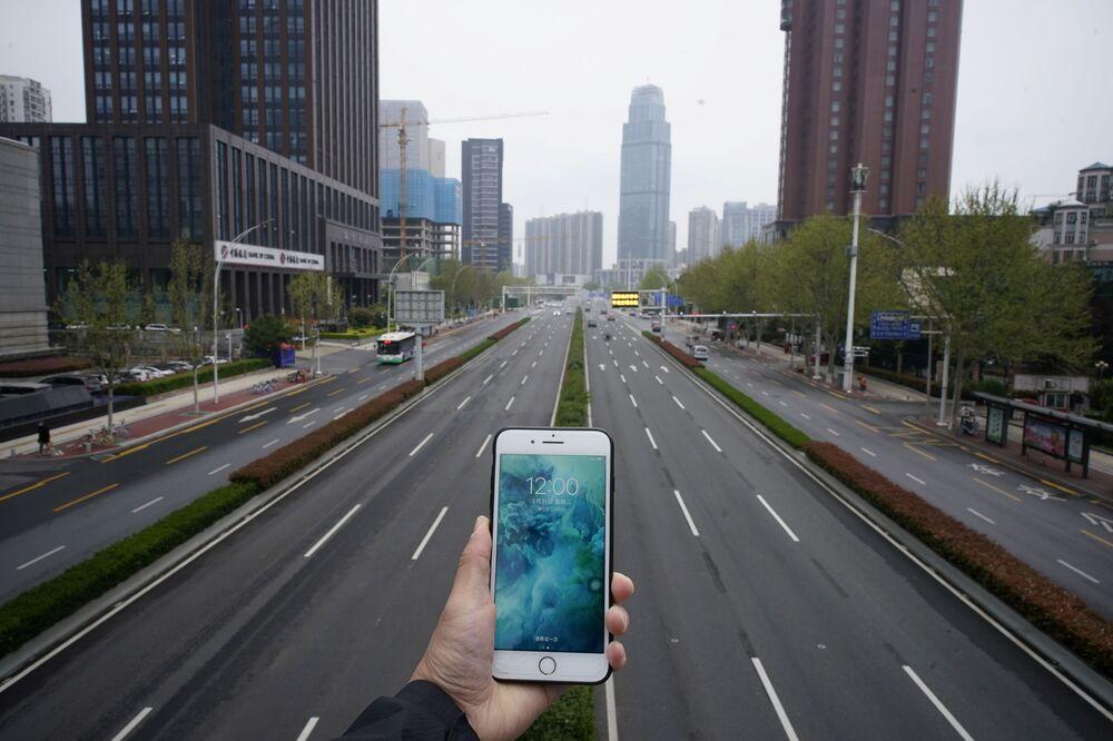 Celular demonstra o horário diante de uma rua vazia em Wuhan, na China