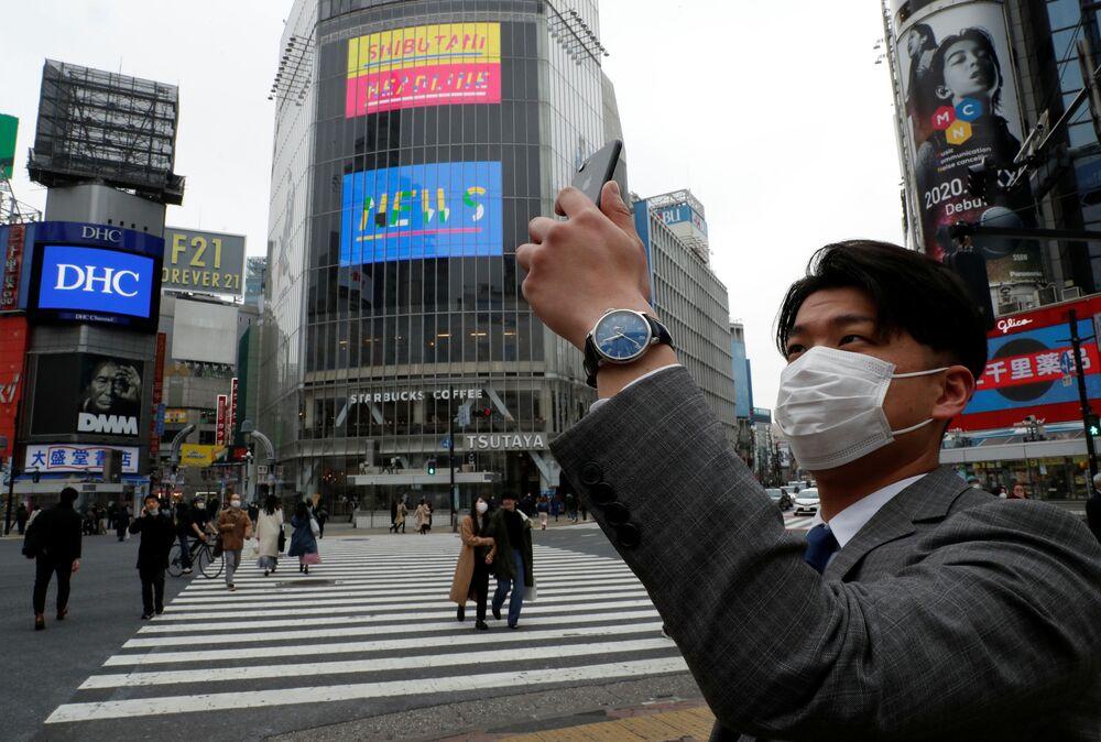 Homem com máscara para se proteger do coronavírus tira uma foto ao meio-dia, em Tóquio, Japão
