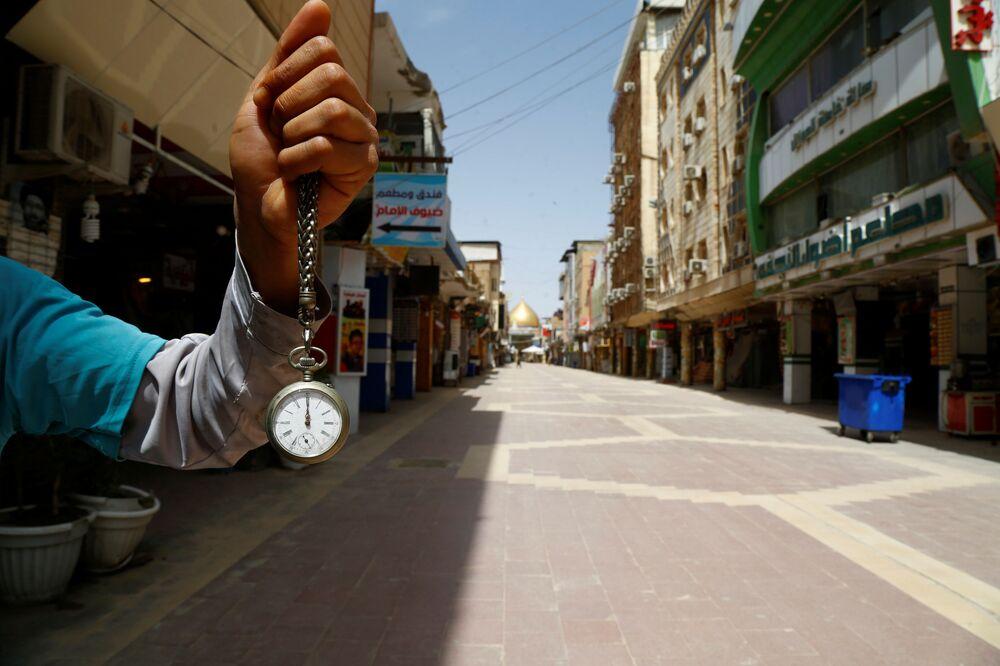 Iraquiano segura relógio de bolso em rua vazia de Najaf, Iraque