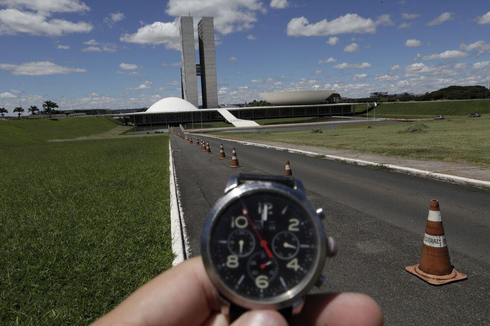 Homem mostra o horário em seu relógio diante do Congresso Nacional em Brasília