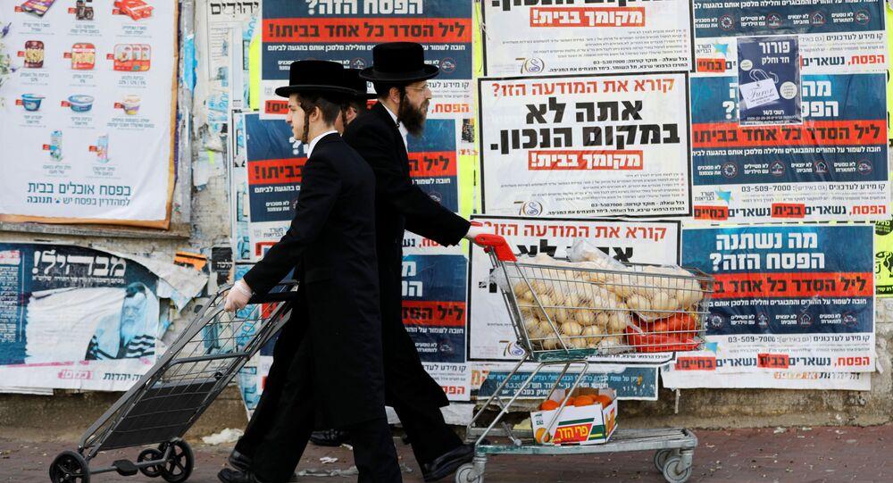 Judeus ultraortodoxos com carrinhos de compras passando em frente a aviso conclamando as pessoas a ficarem em casa devido à pandemia em Israel