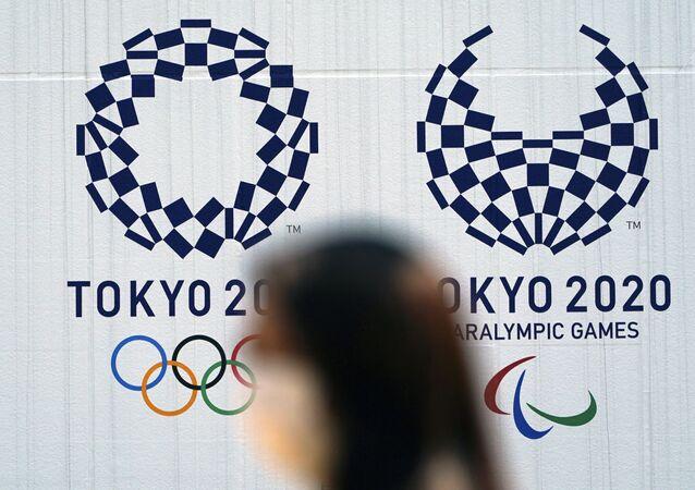 Mulher com máscara passa diante de logo das Olimpíadas de Tóquio