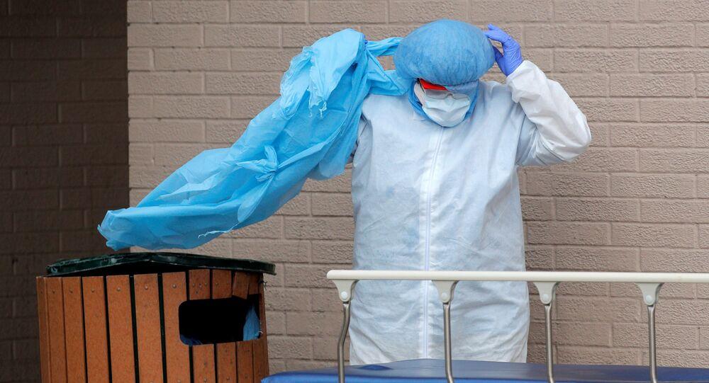 Profissional da saúde retira e descarta equipamento de proteção individual (EPI) durante pandemia do coronavírus, Brooklyn, Nova York, EUA, 2 de abril de 2020