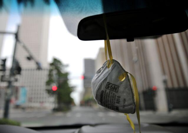 Máscara respiratória N95, da marca 3M, pendurada em retrovisor de carro durante pandemia do coronavírus, Louisiana, EUA, 4 de abril de 2020