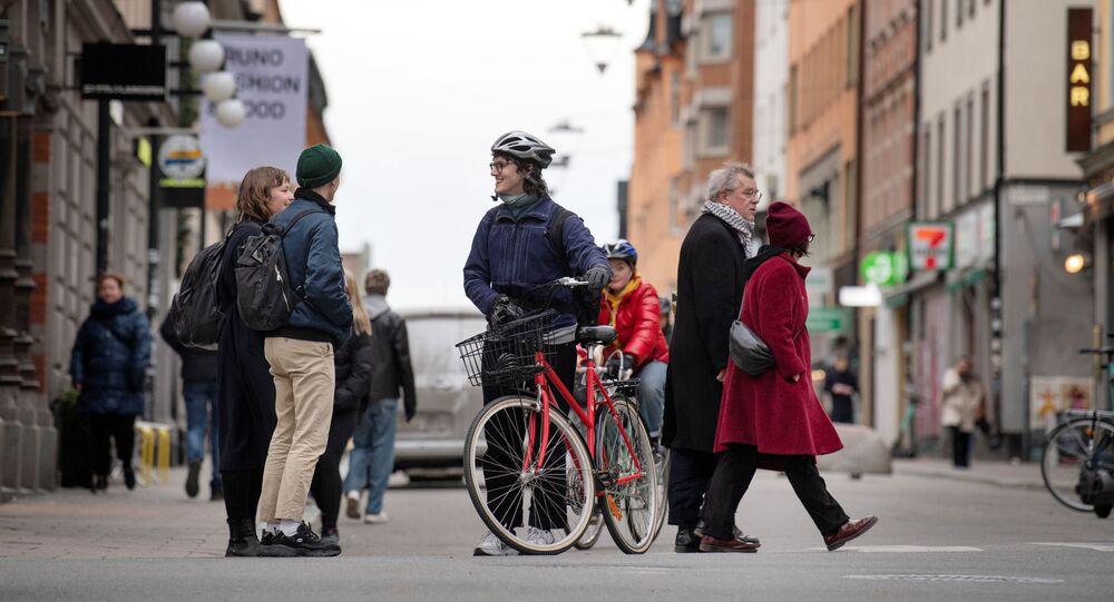 Ciclista conversa com pedestres em meio à pandemia de COVID-19, em Estocolmo, na Suécia, 1º de abril de 2020