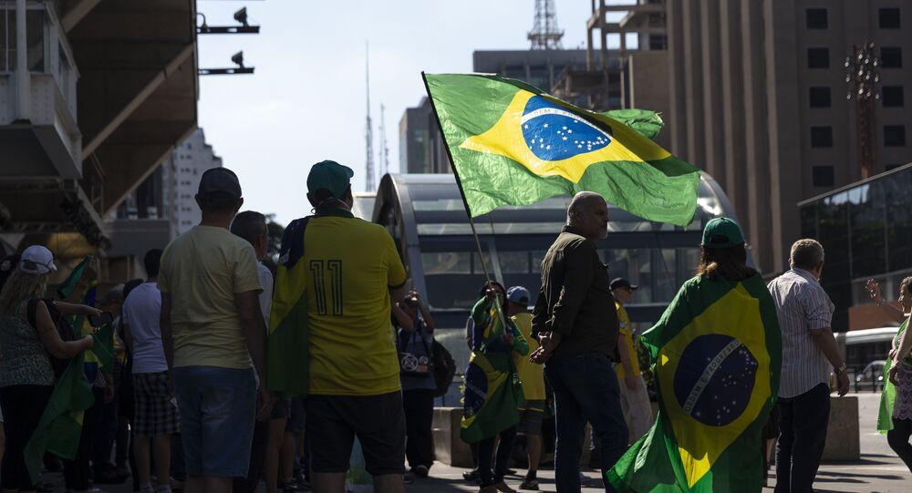 Manifestantes com bandeiras do Brasil e cartazes protestam contra governador de São Paulo, João Doria, que impôs medida de isolamento social para conter pandemia, em frente à Fiesp, 5 de abril de 2020