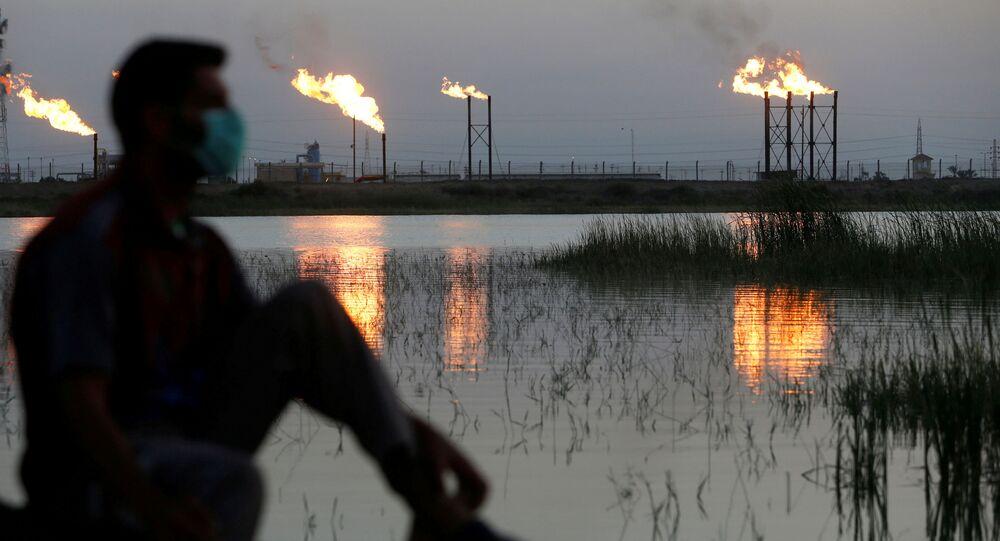 Labaredas emergem de torres no campo petrolífero de Nahr Bin Umar, enquanto um homem usa máscara facial protetora em meio ao surto do coronavírus no norte de Basra, no Iraque, 9 de março de 2020