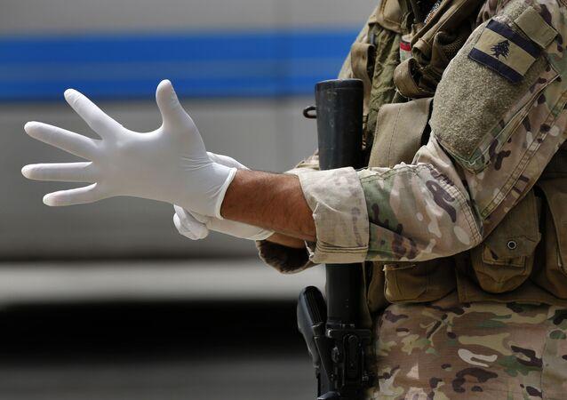 Soldado se prepara para fazer inspeção em passageiros em aeroporto, em meio à pandemia de COVID-19 (foto referencial)