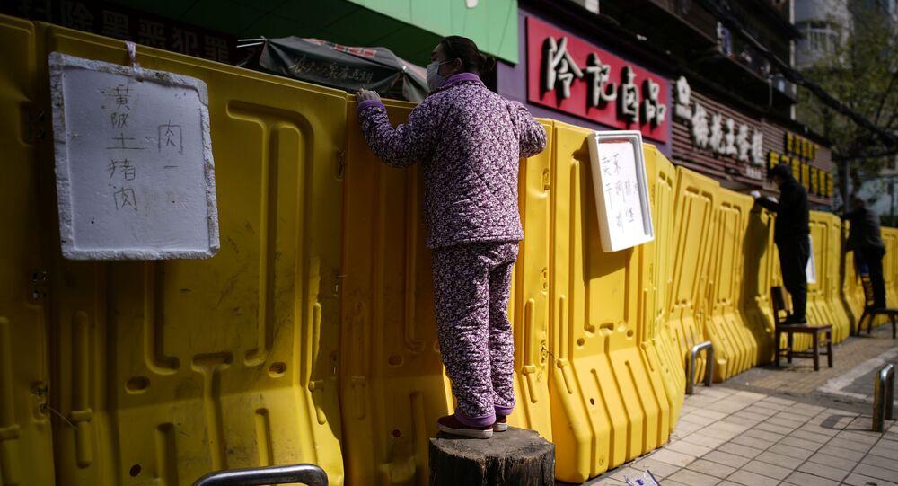 Residentes pagam produtos subindo em cadeiras para espreitar por cima das barreiras montadas para cercar um mercado em uma rua em Wuhan, província de Hubei, o epicentro do surto de coronavírus da China, 1º de abril de 2020