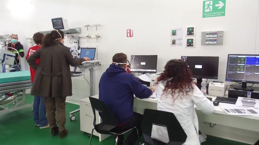Equipe de funcionários do hospital de campanha de Bergamo em frente a computadores, enquanto unidade hospitalar se prepara para atender pacientes com coronavírus