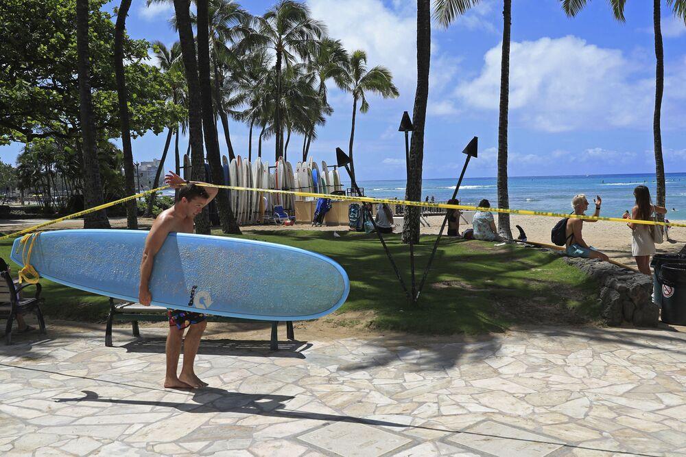 Surfista atravessa faixa de bloqueio de praia