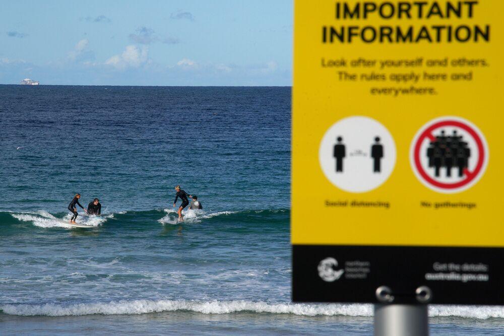 Surfistas em praia australiana em meio à pandemia do coronavírus