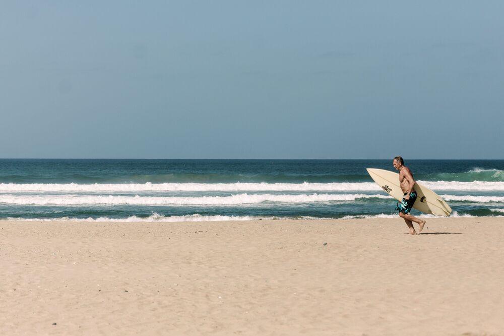 Homem surfa em praia de Dubai em meio à pandemia do coronavírus