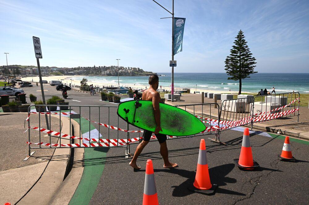 Homem caminha próximo a bloqueio de praia australiana
