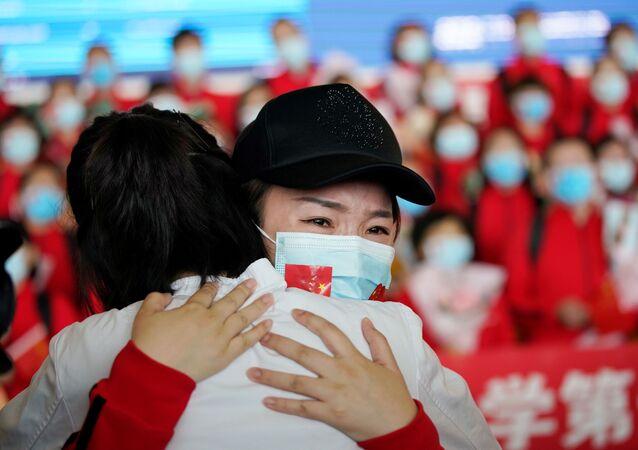 Agentes de saúde chinesas se abraçam no aeroporto de Wuhan, após fim da quarentena na cidade, 8 de abril de 2020