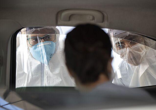 Médicos checam passageiros de um carro em Guarulhos, na Grande São Paulo