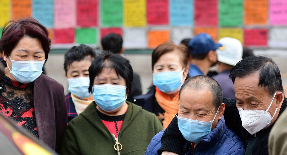 Chineses usando máscaras protetoras olham anúncios de vagas de emprego, na província chinesa de Shandong, 8 de abril de 2020