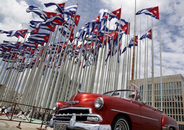 Carro descapotável norte-americano clássico passando ao lado da embaixada dos Estados Unidos em meio a bandeiras cubanas hasteadas na Tribuna Anti-Imperialista, um palco no passeio marítimo de Malecon, em Havana, Cuba, 26 de julho de 2015