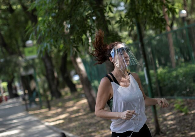 Mulher usa proteção facial para correr no parque na Cidade do México, 8 de abril de 2020