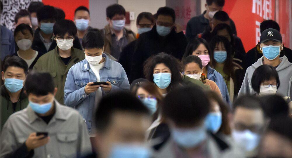 Chineses vestem máscaras rumo a uma estação de metrô em Pequim, na China
