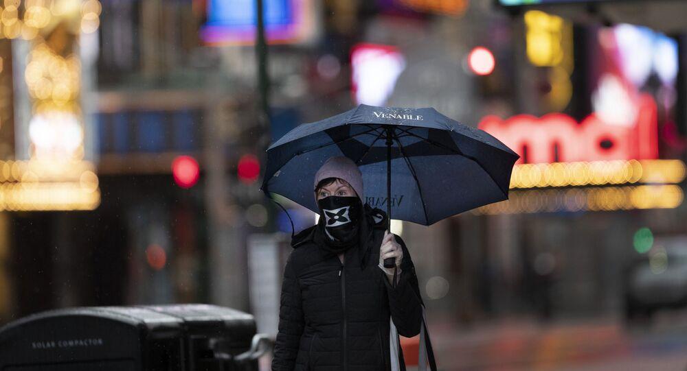 Mulher caminha com máscara sob forte chuva em Nova York, nos Estados Unidos