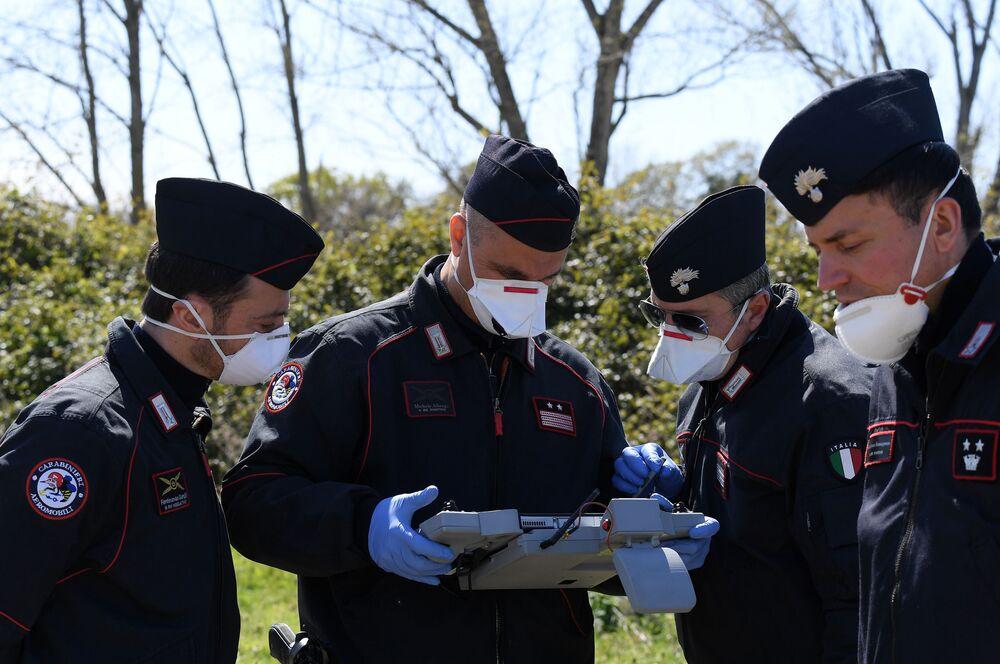 Policiais italianos ao redor de controle de drone