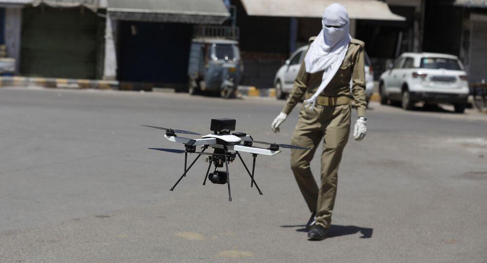 Policial observa drone usado para verificar agrupamentos durante pandemia, Prayagraj, Índia, 3 de abril de 2020 (foto referencial)