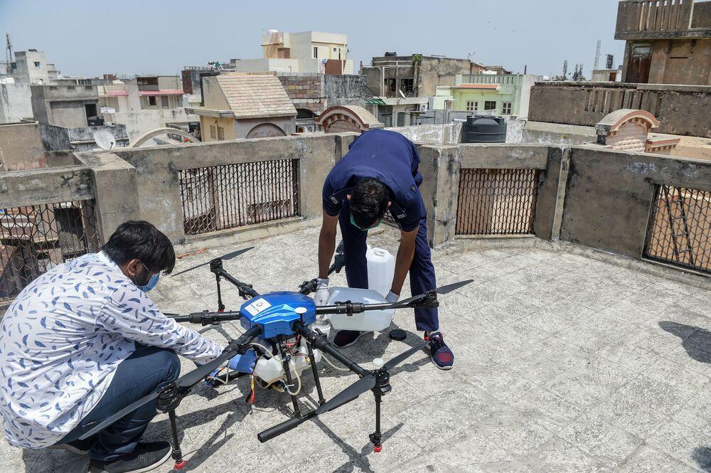 Bombeiro e equipe de operadores em volta de drone na Índia