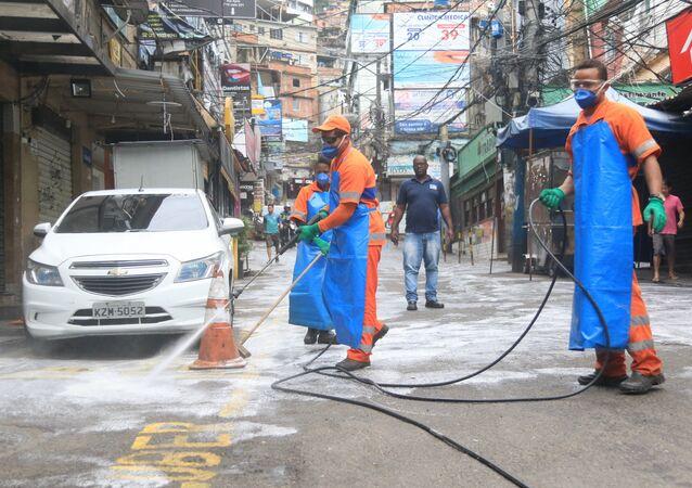 Funcionário da Comlurb fazem a higienização das ruas na favela da Rocinha, na zona sul do Rio de Janeiro