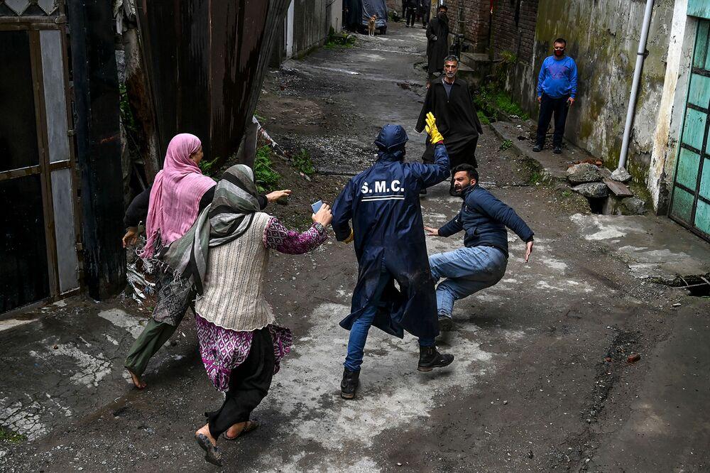 Morador local começa uma briga com um trabalhador municipal acusando-o de não ter desinfetado devidamente sua casa em Srinagar, Índia