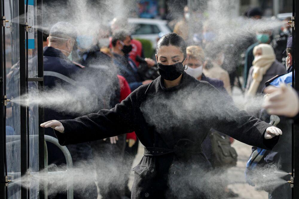 Pessoas são desinfetadas antes de entrar em um mercado em Tirana, na Albânia