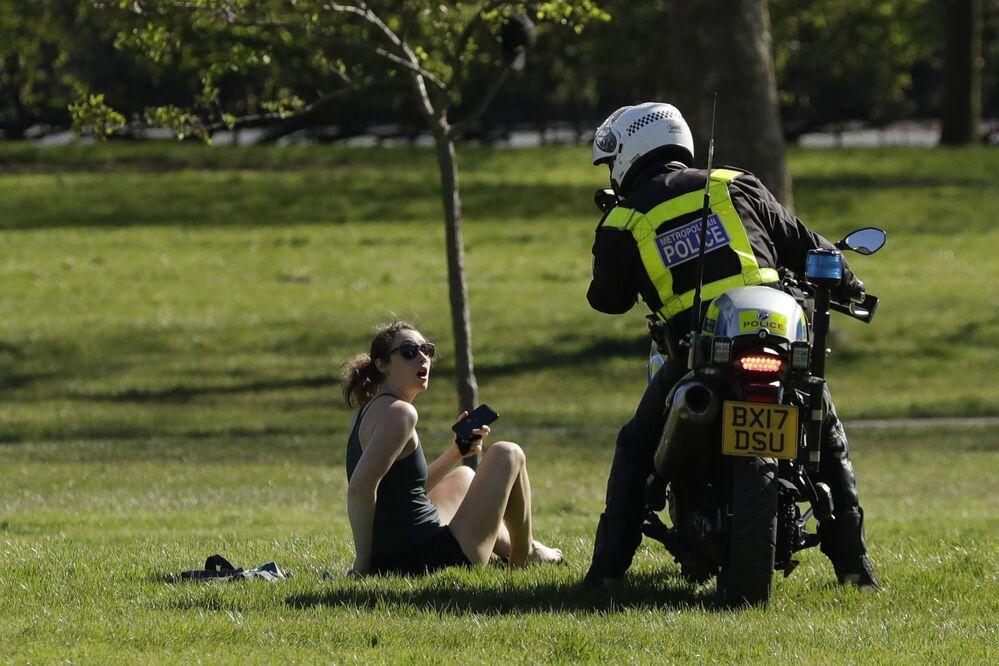 Policial pede a uma visitante para sair do parque devido a medidas restritivas durante a epidemia do novo coronavírus em Londres