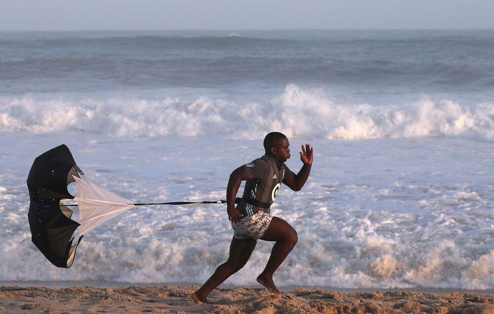 Um homem faz exercícios na praia Recreio dos Bandeirantes em meio ao coronavírus no Rio de Janeiro