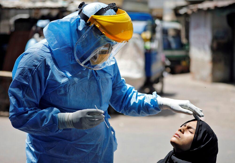 Médico usando equipamento de proteção faz teste de coronavírus a uma mulher em Ahmedabad, Índia