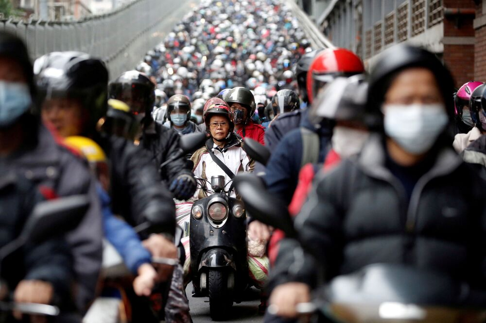 Motociclistas usando máscaras na estrada em Taipé, Taiwan