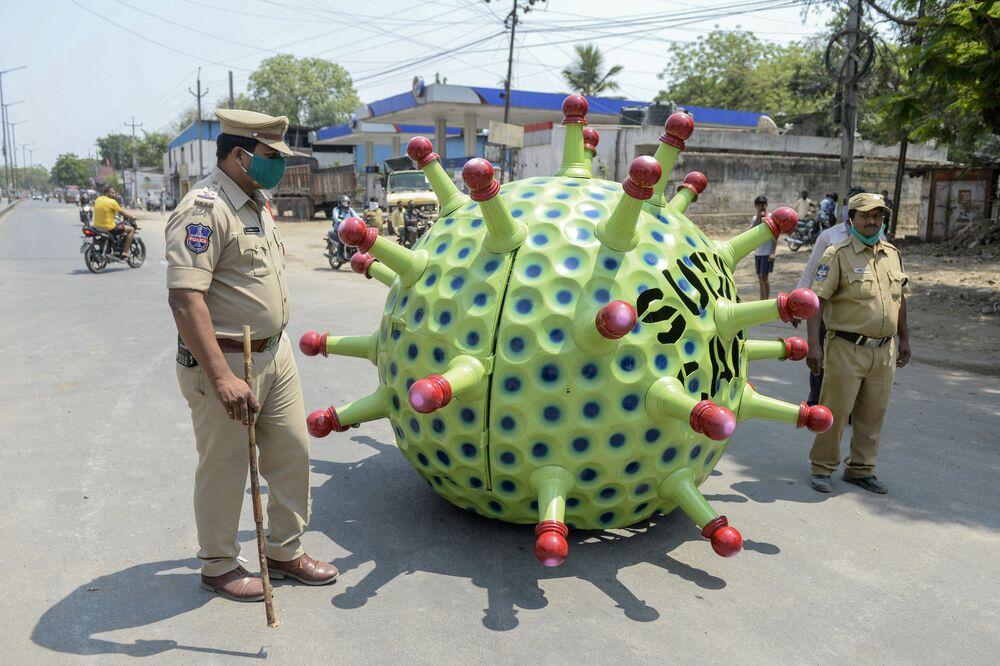 Policiais indianos estão perto de um veículo em forma de coronavírus na cidade de Haiderabade na Índia
