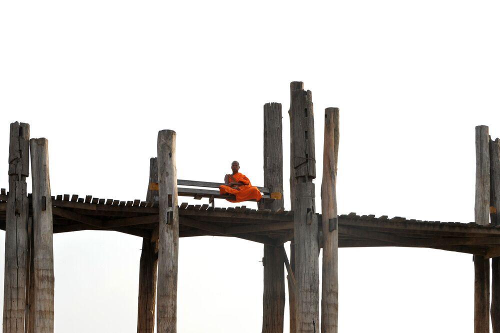 Um monge sentado na ponte de U Bein em Mandalay, no Mianmar