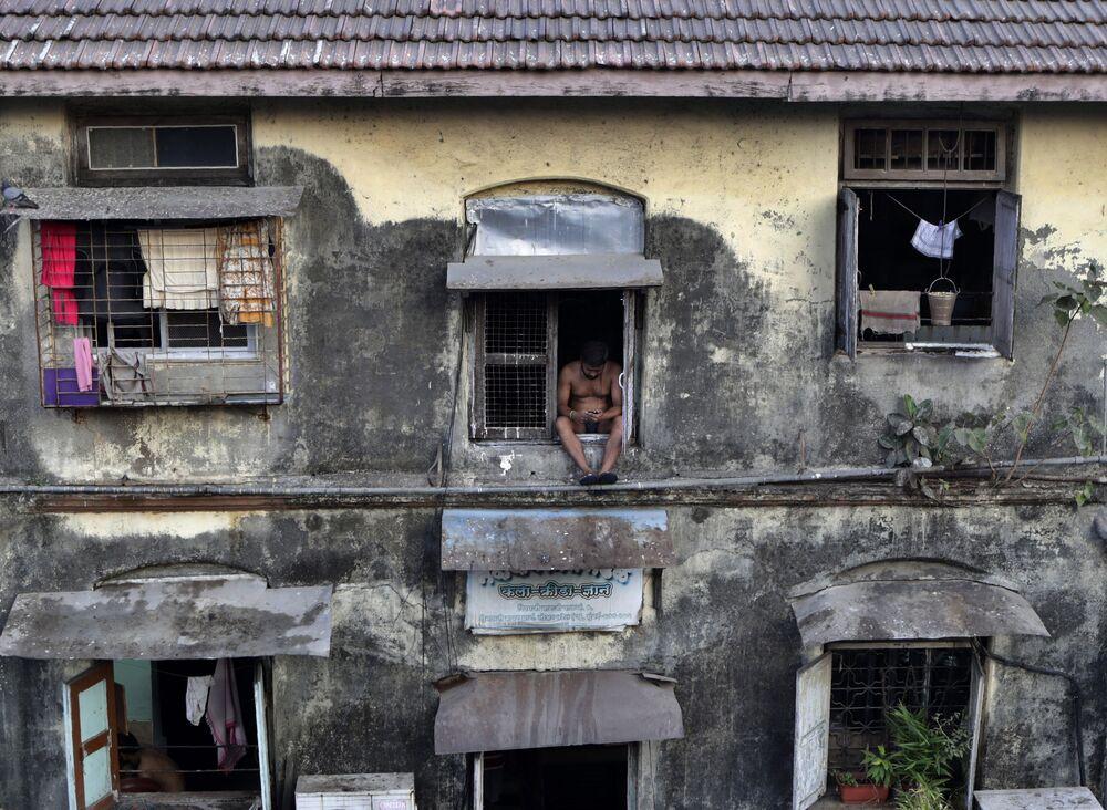 Homem na janela de um apartamento em Mumbai durante o autoisolamento