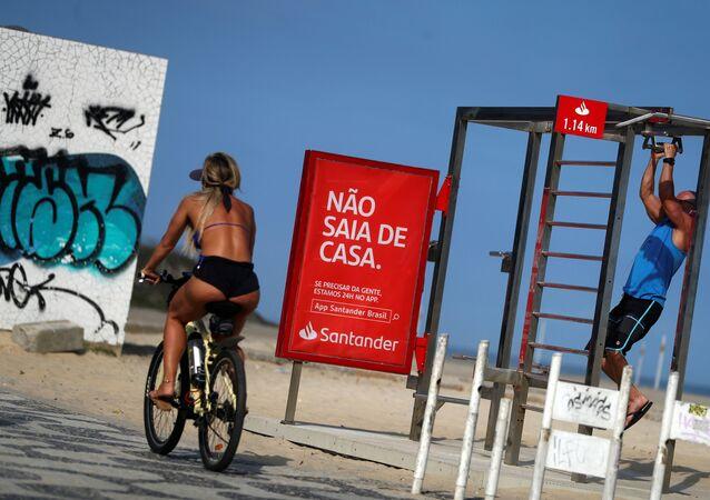 Mulher passa de bicicleta perto de um cartaz que diz Não saia de casa na praia de Ipanema, no Rio de Janeiro, durante a epidemia de coronavírus