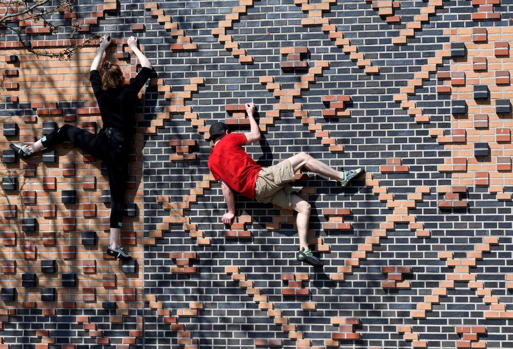Alpinistas Carlotta e Rafael treinam em uma parede de casa durante a quarentena em Hamburgo, na Alemanha