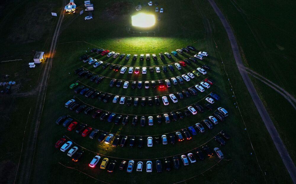 Vista aérea mostra espectadores de cinema sentados em seus carros estacionados a céu aberto na Alemanha