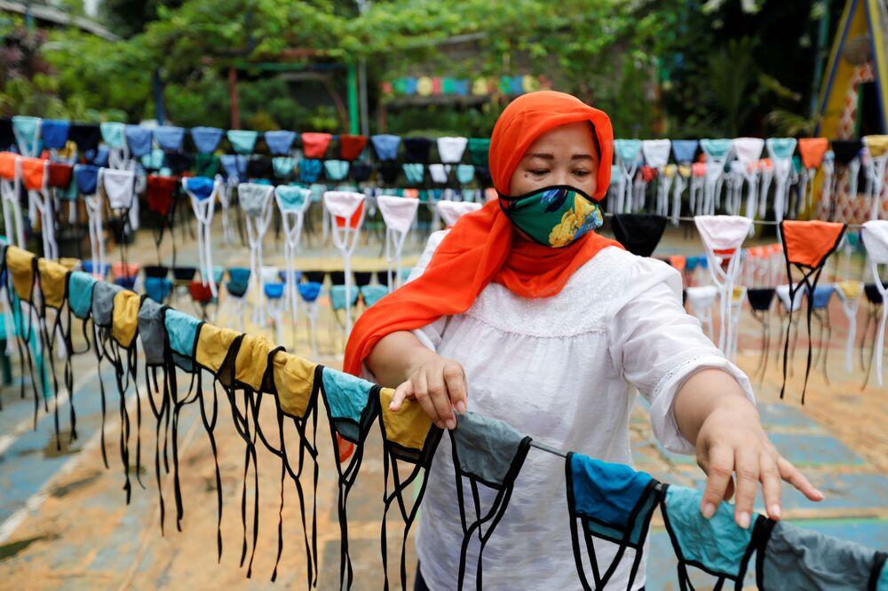 Mulher usa máscara protetora durante a fabricação de máscaras em Jakarta, na Indonésia